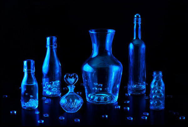Several blue glass bottles with beads and other glass bobbles on a black background.