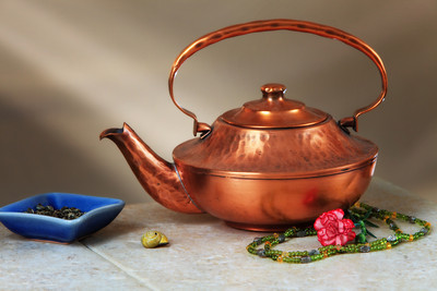 a copper kettle and tea pearls on a tile table with a sunbeam behind
