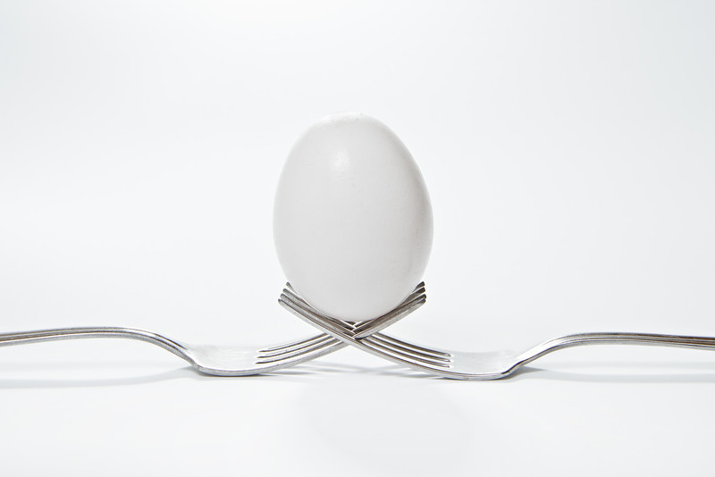 A egg that is set on the top of two forks.  Eggs have so many uses from dieting to making recipes for baking.