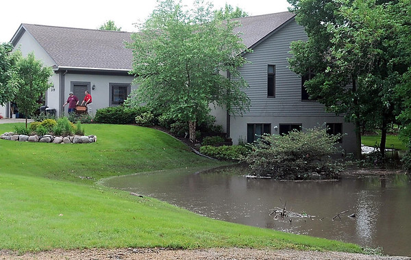 Brian Fowler and Jim Anton move furniture out of Anton's flooded home Wednesday morning. Heavy rains overnight swelled a retaining pond in Anton's back yard, filling his basement with about four feet of vwater.  Photo by Pat Christman