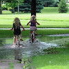 Two girls ride through a puddle in Ray Erlandson Park Wednesday. Photo by Pat Christman