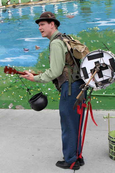 Banjo plus more -steady drum beat to the walk plus tamborine with a swinging pot for donations