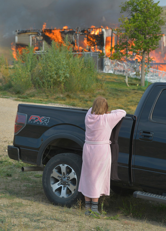 Justin Sheely | The Sheridan Press<br /> A resident looks on as her home burns at 5 Chinook Drive off Decker Road north of Sheridan on Wednesday. Sheridan Fire-Rescue and Goose Valley Volunteer Fire Department responded to the call of a structure fire around 5 p.m. The resident and her dog made it out safely. No injuries were reported. The house was a complete loss.