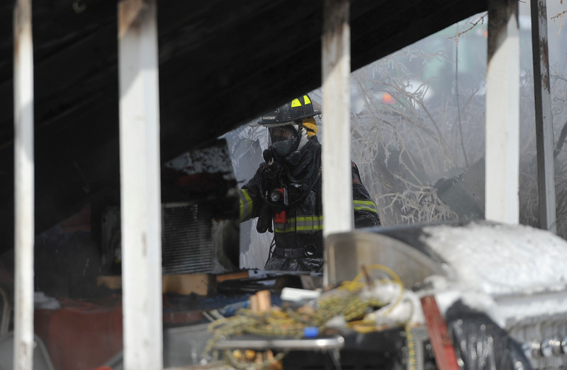 Justin Sheely | The Sheridan Press<br /> <br /> A Goose Valley firefighter assesses part of the house in response to a structure fire at a residence on Coffeen Avenue Wednesday, Feb. 20, 2018. Sheridan Fire-Rescue, Goose Valley Volunteer Fire Department and Rocky Mountain Ambulance responded to a structure fire call at 9:58 a.m. Wednesday at 5461 Coffeen Ave.