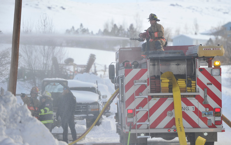 Justin Sheely | The Sheridan Press<br /> <br /> Sheridan Fire-Rescue's Jon Syring operate the hose on the deck of a fire engine in response to a structure fire at a residence on Coffeen Avenue Wednesday, Feb. 20, 2018. Sheridan Fire-Rescue, Goose Valley Volunteer Fire Department and Rocky Mountain Ambulance responded to a structure fire call at 9:58 a.m. Wednesday at 5461 Coffeen Ave.