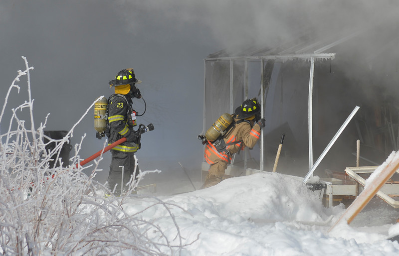 Justin Sheely | The Sheridan Press<br /> <br /> Goose Valley, left, and Sheridan Fire-Rescue firefighters assess part of the house in response to a structure fire at a residence on Coffeen Avenue Wednesday, Feb. 20, 2018. Sheridan Fire-Rescue, Goose Valley Volunteer Fire Department and Rocky Mountain Ambulance responded to a structure fire call at 9:58 a.m. Wednesday at 5461 Coffeen Ave.