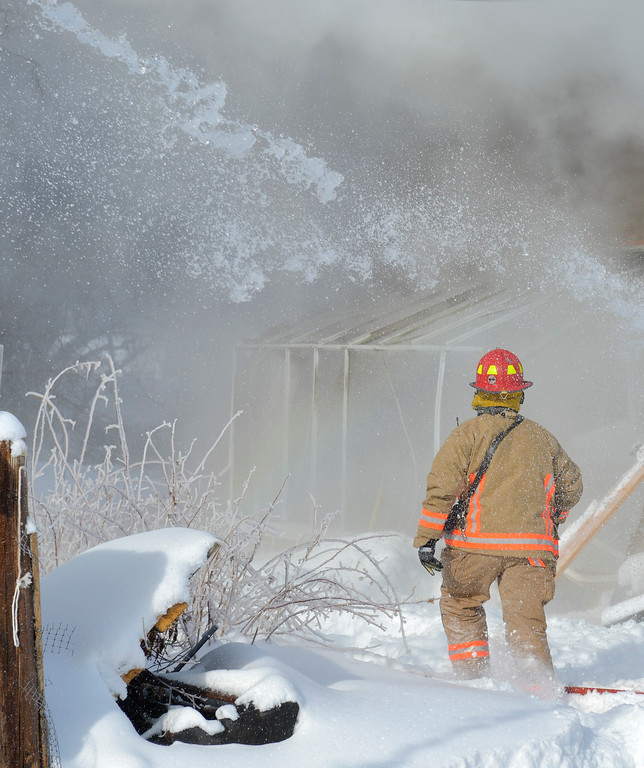 Justin Sheely | The Sheridan Press<br /> <br /> Sheridan Fire-Rescue captain Gary Harnish walks by as water shoots from a fire engine in response to a structure fire at a residence on Coffeen Avenue Wednesday, Feb. 20, 2018. Sheridan Fire-Rescue, Goose Valley Volunteer Fire Department and Rocky Mountain Ambulance responded to a structure fire call at 9:58 a.m. Wednesday at 5461 Coffeen Ave.