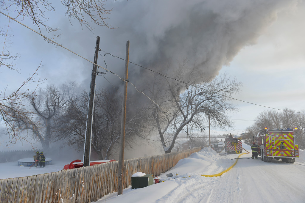 Justin Sheely | The Sheridan Press<br /> <br /> Smoke rises as firefighters respond to a structure fire at a residence on Coffeen Avenue Wednesday, Feb. 20, 2018. Sheridan Fire-Rescue, Goose Valley Volunteer Fire Department and Rocky Mountain Ambulance responded to a structure fire call at 9:58 a.m. Wednesday at 5461 Coffeen Ave.