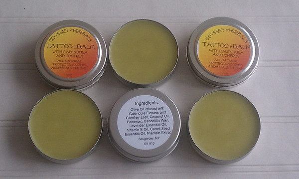 Odyssey Herbals Tattoo Balm  Made with all natural ingredients -  Olive Oil infused with Calendula Flowers and Comfrey Leaf, Coconut OIl, Beeswax, Candelilla Wax, Lavender Essential OIl, Vitamin E Oil, Plantain Extract, Carrot Seed Essential Oil.
