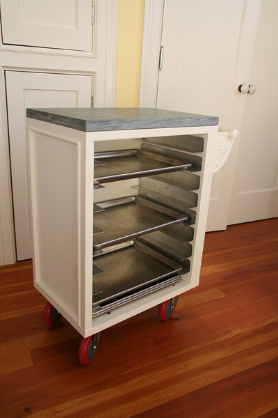 Kitchen cart.  My design and build.  Top is soapstone same as kitchen counters.  Holds standard half-sheet baking pans.  Rolls to wherever it will be most convenient at the moment.