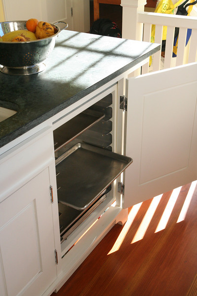 Cupboard door hides cart, opens to access sheet pans when cart is stowed under counter.