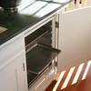 Cupboard door hides cart, opens to access sheet pans when cart is stowed under counter.