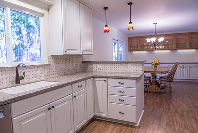 Boothby Kitchen Remodel Bright white cabinets with quartz counters and basketweave tile splash.