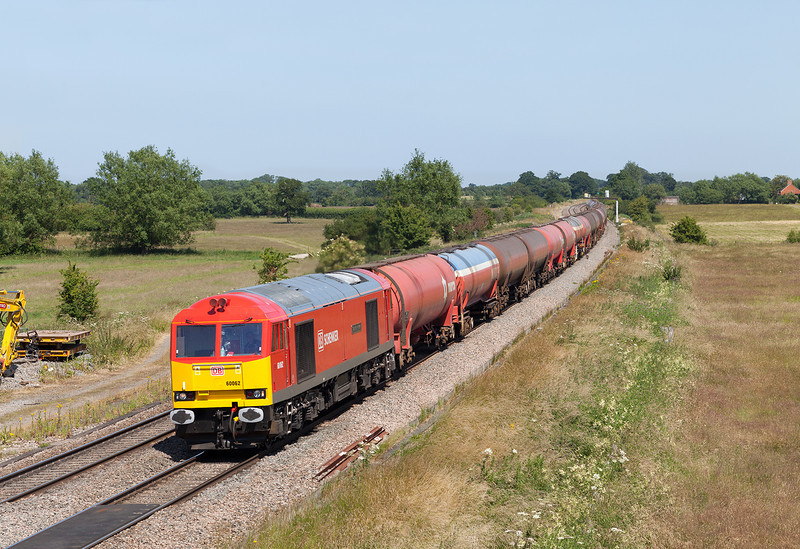 With a friendly wave and a toot from the driver, an immaculate 60062 'Stainless Pioneer' passes Ashbury crossing, Shrivenham with the 6B33 13.00 Theale-Robeston empty Murco oil tanks.11.7.13
