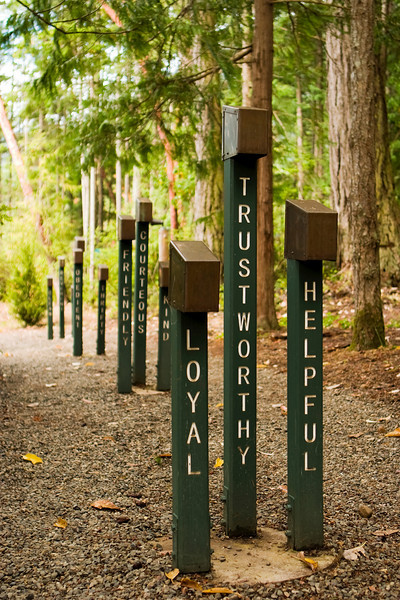 Loyal, trustworthy and helpful are three adjectives that describe boy scouts. These signs line a dirt path to a campfire ground at a boy scout camp.