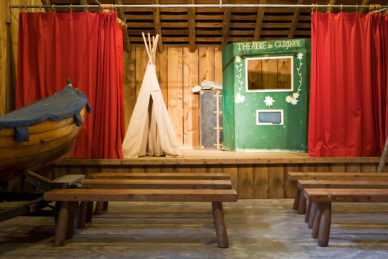 A theater at a summer camp that is used for occasional performances. The stage has a few props including a teepee, a booth, and a boat for use by the actors.