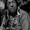 """This is Ben Black Elk. This is where my photographic quest starts in the summer of my 18th year. Native Americans say we reach an age when we would gladly trade the rest of our life for a single summer in our youth. Should that time come, I'll take the summer of 1965 when Lenny Kaczor and I  walked off to look for America, and discovered old Ben. This photo of Ben gets me my first newspaper photography job in 1966 but the job costs me my student draft deferment. But the photography experience makes me a Navy photographer.<br /> <br /> Even if one only gets a moment in life to repeat, I'll take that instant of epiphany, under the dark cloth, when the old Sioux prophet came to focus on the ground glass of my antique press camera. So compelling is the surging current in my soul, only my tripod keeps shaking hands from blurring this image of Black Elk. <br /> <br /> Young and foolish, I think I've discovered an old Indian in full Sioux regalia who happened to be sitting around Mount Rushmore National Monument. Instead, Black Elk, discovers me. I don't know then Ben is considered America's most photographed Native American in history.  I take my photographs and he calls me to sit with him. <br /> <br /> He tells me the story of the first photographer he had ever seen when he was a young man, like me. """"The man had a camera just like yours,"""" says Ben gestering to my rare 3 1/4 X 4 1/4 press camera, """"The photographer scared my people with his magic because we felt he captured our spirits with his strange black box."""" Ben goes on to explain that time, education, and understanding has taught him differently. Yet part of him can't shake his original belief that cameras steal a bit of our souls. <br /> <br /> From that conversation forth, I know I'm a photographer. I go off into the world with a new understanding of my place in the grand scheme of  things. I take a piece of Black Elk's force with me, and live the life of a spirit catcher."""