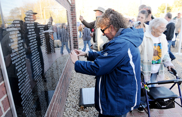 Don Knight | The Herald Bulletin<br /> Residents take photos of names inscribed on Summitville's new monument honoring veterans on Saturday. The monument honors locals who served in the military.