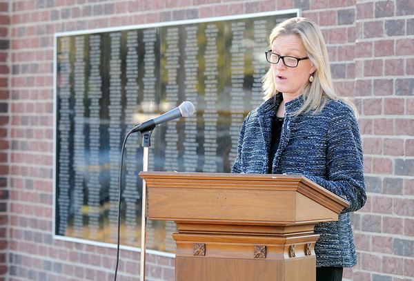 Don Knight | The Herald Bulletin<br /> Tanya Wilhoite of Wilhoite Monuments reads the over 500 names inscribed on a monument honoring veterans in Summitville on Saturday.