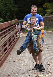 James Bauer plays with Chase Sexton, age 6, on the bridge at Cascade park. photo by Ray Riedel