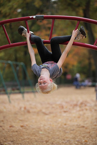 Abby Morningstar, age 8, of Elyria hangs upside down in the playground at Cascade park. photo by Ray Riedel
