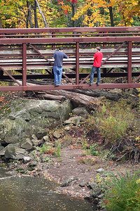 Two young men high above the river on the outside of the foot bridge in Cascade park on Sunday. photo by Ray Riedel