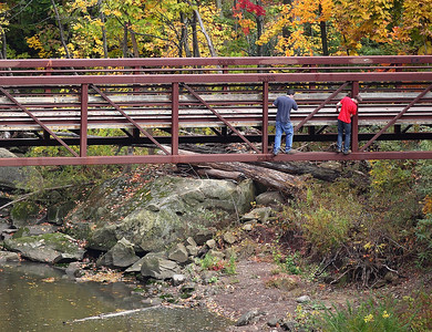 Two young men take an unconventional journey along the outside of the foot bridge in Cascade park on Sunday. photo by Ray Riedel