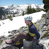 Noal chalking up with Zen-like focus for the first pitch. Thick snow blankets Desolation Wilderness in the background.