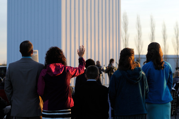 Susan Logan of Mason raises her hand in song while attending Easter sunrise service with her family at The Cross at the Crossroads Sunday morning.<br /> Chet Piotrowski Jr./Piotrowski Studios photo