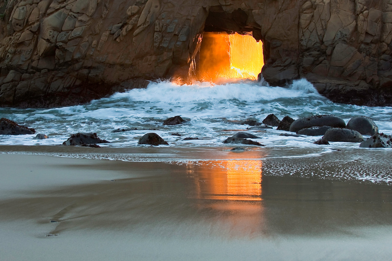 Surging water through the doorway arch at Pfeiffer Beach.