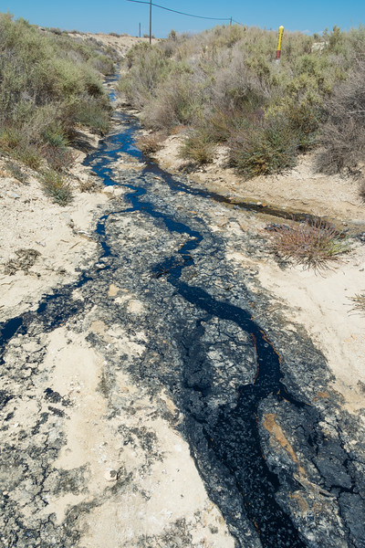 Crude oil leaking out into a dried watercourse, not far above McKittrick Oilfields on Highway 58, west of Buttonwillow, California, USA, June 2015. [McKittrick-HWY58 2015-06 003 CA-USA]