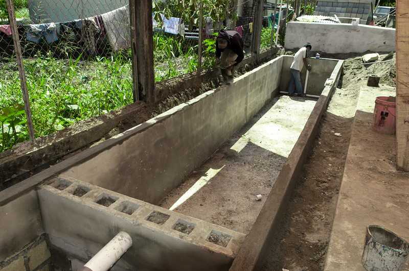 Construction of a Horizontal Sub-Surface Flow wetland for sustainable and environmentally friendly wastewater treatment, showing the outlet, at YAJASI in Sentani, Papua, 2010. [Papua Sentani 2010-05 007 YAJASI_SSFCW]