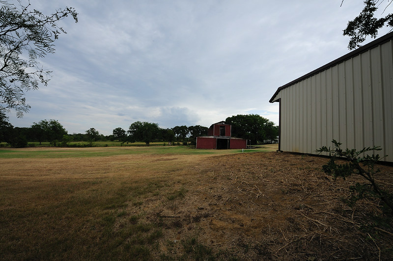 VIEW ALONG SOUTH FENCE OF<br /> NEIGHBOR'S OLD BARN AND NEW HORSE<br /> STALLS TO THE RIGHT