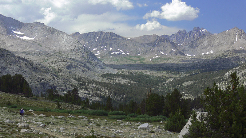 "Starting around 2pm the skies were clouding-up and as things were looking rather ""iffy"" I headed back towards Bench Lake. Here's a 16:9-aspect ratio pic showing the broad expanse of Upper Basin leading up to the Palisades under the cloud on the right. I met a few people while on the JMT including this fellow (he gives the scene perspective) and some other solo backpackers, including a fellow from Mexico (!) doing a loop from the west side and a gal doing the classic Tuolumne-Whitney trek by herself."