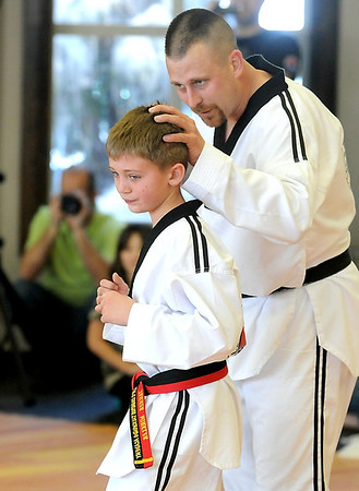 Pat Christman<br /> Colby Winkler encourages his son Tanner during warm ups before the pair test for highter black belt degrees Saturday at Lee's Champion Tae Kwon Do in Mankato.