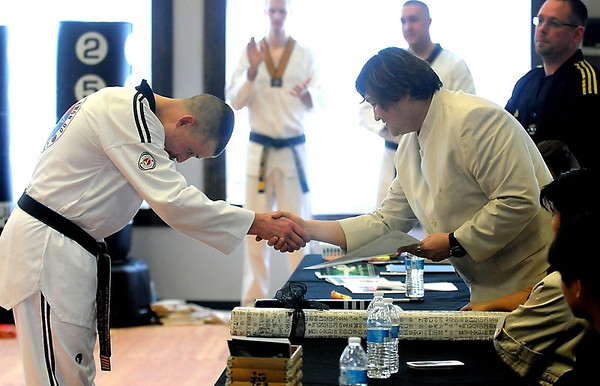 Pat Christman<br /> Colby Winkler is congratulated by Grand Master Yong Hyeok Lee after testing to his sixth degree black belt Saturday.