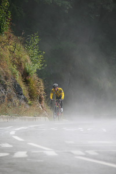 Road cyclist rides through the mist on Alpe d'Huez, France