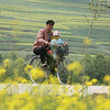 Old man cycling with a baby, Qinghai, China