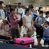 Bored passengers waiting for their luggage at the baggage carousel at Don Muang airport in Bangkok, Thailand in August 2017