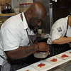 Bravo Television's Top Chef contestants Kenny Gilbert (Season 7) and Arnold Myint (Season 7) plating for their guests.