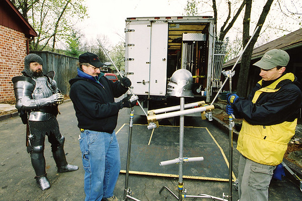 Karl Kindt III, far left in armor, watches as his helmet is rigged for a shot in a television commercial filmed by Technisonic Studios of St. Louis, Missouri.