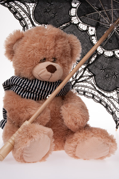 teddy bear with a lace parasol and a stripey scarf isolated on white background