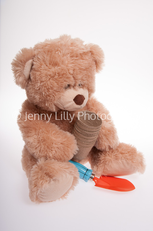 teddy bear with gardening tools and pots, isolated on white background
