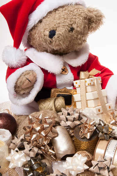 teddy dressed as Santa with wrapping ribbon and bows, isolated on white background