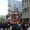 The men on the silver chariot giving blessed flowers, fruit, scarves, and ashes to the crowd