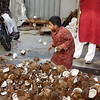 A little boy picking out the less-damaged coconuts to throw again and break some more!