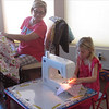 Grace learns to sew with Grandma Brenda training.