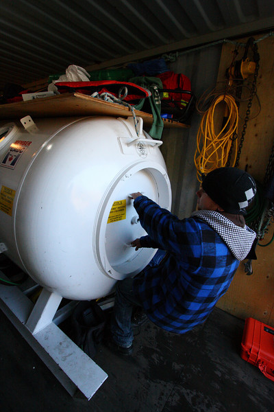 With both divers in the chamber, a seal on the chamber door needs to be established, a good tug will allow even a tiny amount of air pressure to seal the door with hundreds of pounds of force