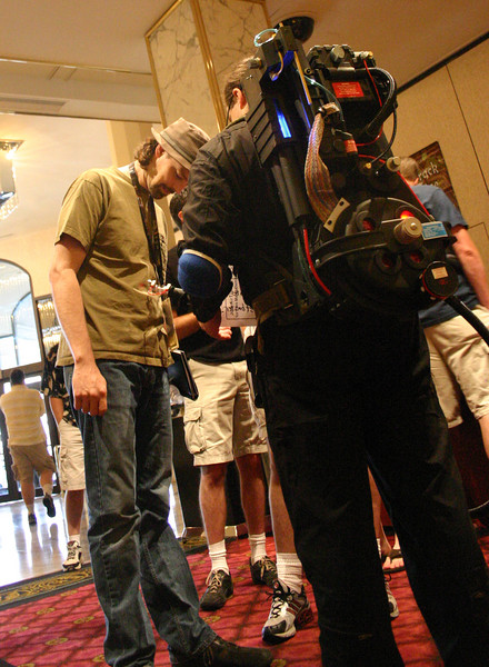 An amateur ghostbuster shows off the output nozzle of his Proton Pack to a Defcon attendee. The device was built to exacting standards based on design documents created for the propmasters of the movie.Too bad the guy's jumpsuit didn't quite cut the mustard.