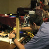 One of the robot operators at Defcon Bots tweaks a piece of hardware that helps control his bot's machine gun.